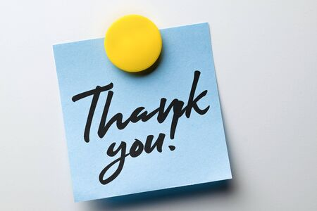 Close-up note with words of thanks written in handwritten font attached with a magnet to a metallic white surface.