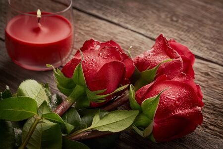 Beautiful romantic background of red roses and aroma candle on a wooden background.