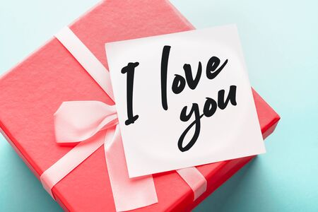 Close up of a red gift box with a note with the words I love you on a blue background: concept of assurance of love and holiday gifts.