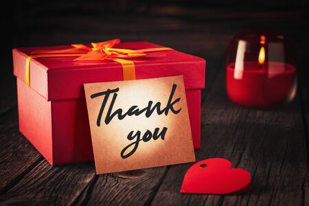 A note with the words Thank you next to a red gift box and a burning candle: a holiday gift concept or an expression of gratitude