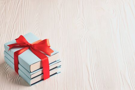 Books tied with ribbon on a wooden background with copy space: concept of donating books.