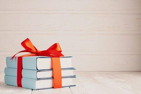 Een stapel van drie boeken vastgebonden met een rood lint met een strik en kopieerruimte: het concept van een goed boek - een goed cadeau.