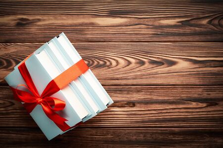 Stack of books in a gift ribbon on a colored background on a wooden background with place for text: concept of education and donation of books.