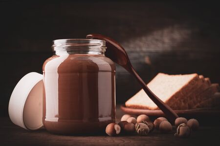 Jar of chocolate-nut pasta with slices of fresh white bread and hazelnuts on wooden background.