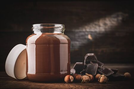Jar of chocolate-nut pasta with pieces of bread and hazelnuts with pieces of chocolate on wooden background