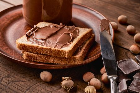 Chocolate nut pasta with slices of toast bread in a plate on a wooden background. Stock fotó