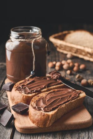 Slices of bread with chocolate nut cream on a cutting board and pieces of chocolate on a wooden background. Vertical shot.