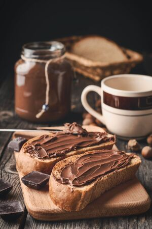 Slices of bread with chocolate nut cream and a jar of cream with a cup on a wooden background. Vertical shot. Stock fotó