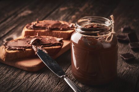 Close up of jar of chocolate nut cream and slices of bread with pasta on wooden background.