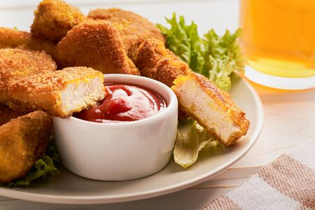 Close-up of a slice of chicken nuggets in ketchup in a plate with a bunch of nuggets. Stock fotó