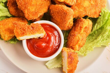 Top view sliced chicken nuggets in ketchup in a plate with a bunch of nuggets and lettuce.