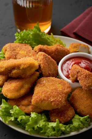 A plate of cooked chicken nuggets with ketchup and a glass of beer on a dark background. Vertical frame.
