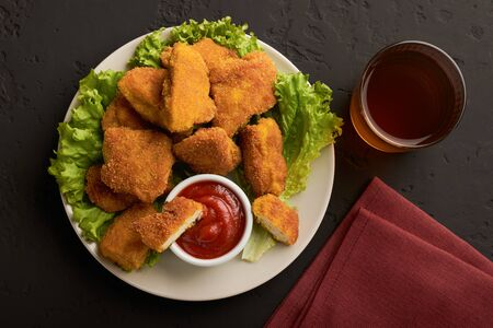 Top view plate of cooked chicken nuggets with ketchup and a glass of beer on a dark background. Stock fotó