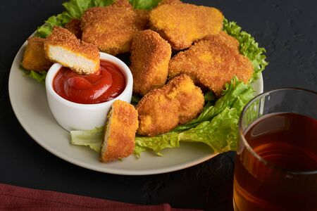 A plate of fried chicken nuggets with ketchup and a glass of beer with a cloth napkin on a dark background. Stock fotó
