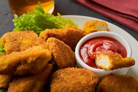 A plate full of fried chicken nuggets with ketchup and a glass of beer with a cloth napkin on a dark background.