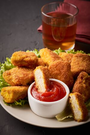 A slice of chicken nuggets in ketchup on a plate filled with chicken nuggets and a glass of wine on a dark background vertical shot.