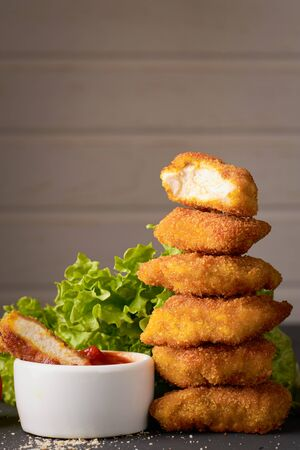 A stack of fried chicken nuggets and a bowl of ketchup and lettuce with copy space. Stock fotó