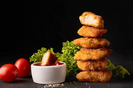 A stack of chicken nuggets and a bowl with ketchup and lettuce on a dark background.