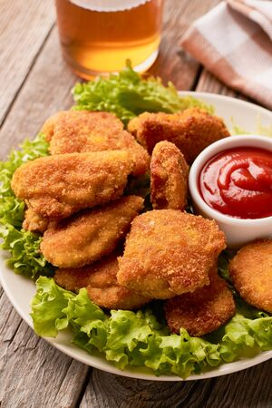 Close up of chicken nuggets with ketchup and lettuce on a wooden background.
