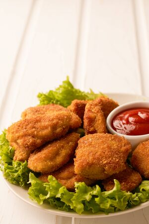 Chicken nuggets with ketchup and lettuce on a white wooden background with copy space.