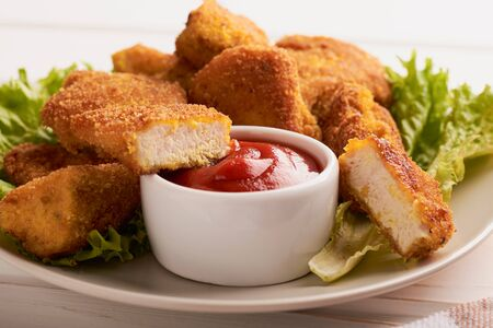 Breaded chicken nuggets in a plate with ketchup and lettuce. Stock fotó
