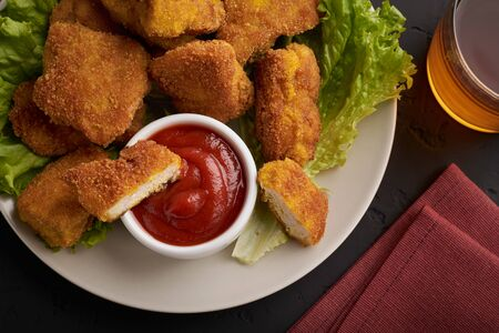 Top view plate with chicken nuggets and ketchup and a glass of beer on a dark background.