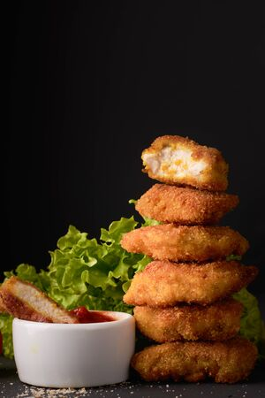 Chicken nuggets with ketchup and lettuce on a dark background with copy space