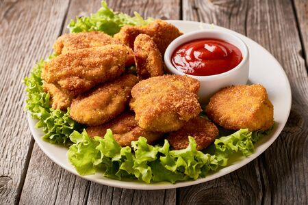 Close up plate with fried chicken nuggets with lettuce and ketchup. Stock fotó