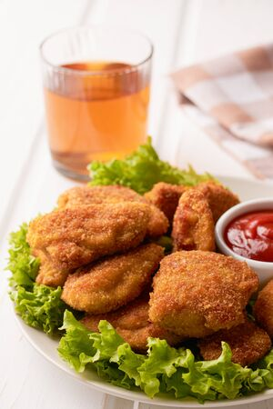 Chicken nuggets with ketchup and lettuce in a plate on a white wooden background. Vertical shot. Stock fotó