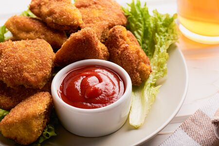 Close-up of a plate filled with cooked chicken nuggets with lettuce and ketchup on the table. Stock fotó