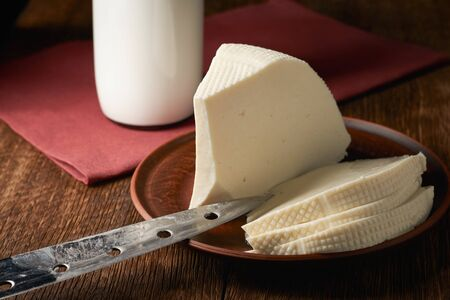 Home-made feta cheese and a bottle of milk as a raw material for the product.