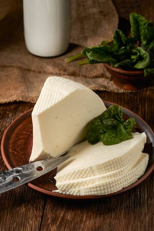 Homemade brynza cheese cut into pieces and a bottle of milk as raw material for the product. Stock fotó