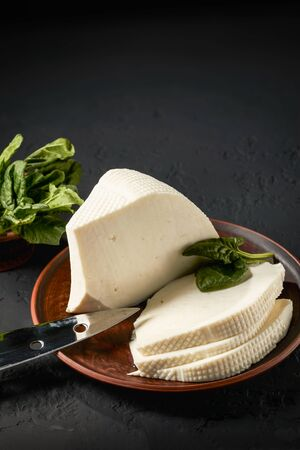 Homemade feta cheese sliced in pieces with spinach leaves on a dark background with copy space: concept of a dairy product and organic food.
