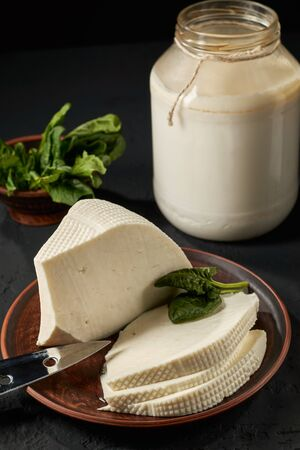 Homemade feta cheese sliced into slices and a can of sour milk as a raw material for the product: the concept of a dairy product and organic food.