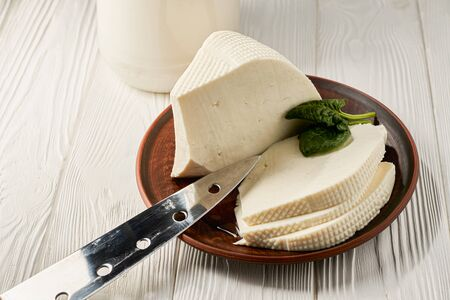 Homemade feta cheese in a plate and a can of sour milk as raw material for the product on a white wooden background with.