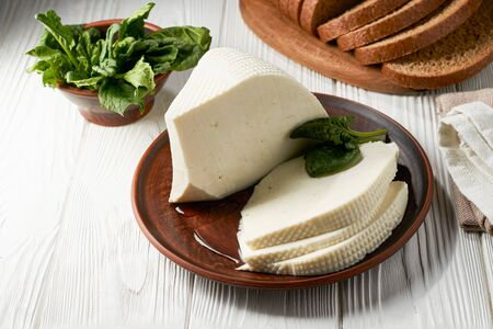 Homemade feta cheese in a plate on a white wooden table.