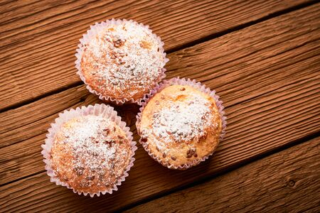 Top view muffins sprinkled with powdered sugar and flax seeds on a wooden background.