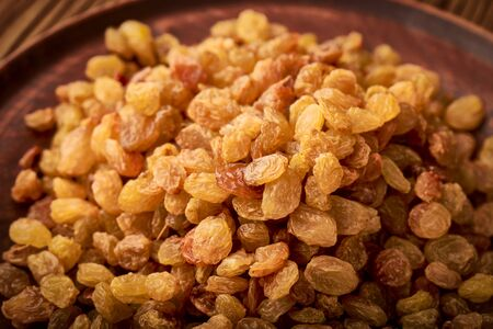 Heap raisins dried grapes plate: organic food concept.