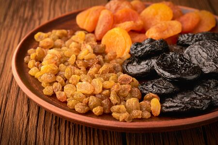 Assortment of dried fruits and raisins and apricots with plums in a plate on a wooden background.