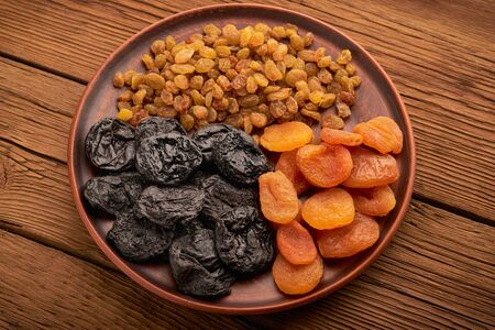 Top view set of dried fruits and raisins and apricots with plums in a plate on a wooden background.