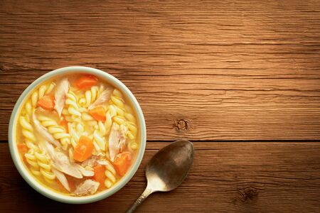 Top view of a bowl of chicken noodle soup and spoon on a wooden rustic background with copy space. Stock fotó