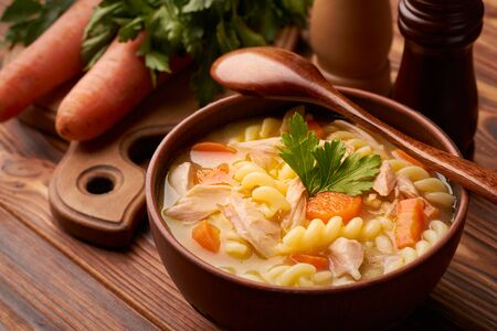 Bowl of chicken noodle soup with a wooden spoon and cutting board with carrots and parsley on a wooden rustic table. Stock fotó