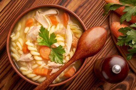 Top view of a bowl of chicken noodle soup with a wooden spoon and cutting board with carrots and parsley on a wooden rustic table.