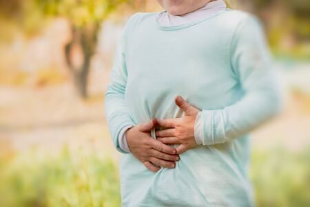 Girl holding her hands on her stomach: concept of pain, poisoning, symptoms. Stock fotó