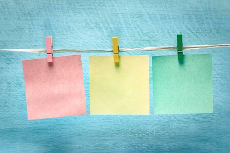 Multi-colored blank notes on a blue wooden board background.