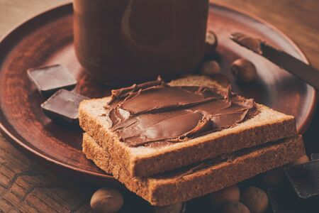 Chocolate-nut paste spread on bread toasts in a plate with a jar.