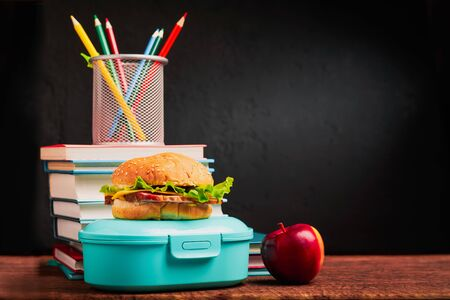 Sandwich and lunch box on the table with a stack of books with copy space: school food concept.