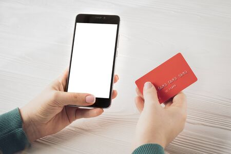 Woman hands holding smartphone with blank screen and red credit card: concept of online banking, online trading, e-commerce.
