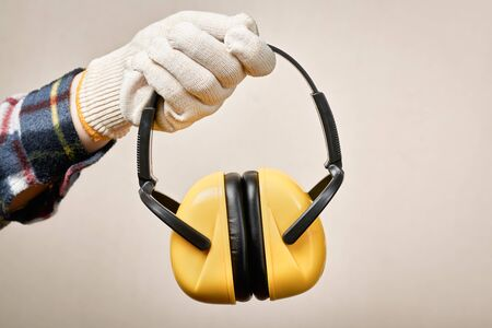 Workers hand giving protective earphones: hearing protection and labor protection concept.
