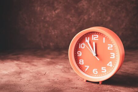 Round clock showing time five minutes to twelve with copy space.